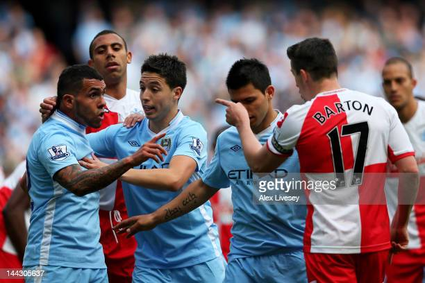 Carlos Tevez of Manchester City clashes with Joey Barton of QPR after being fouled during the Barclays Premier League match between Manchester City...