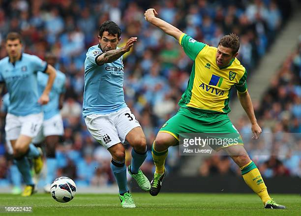 Carlos Tevez of Manchester City holds off the challenge of Grant Holt of Norwich City during the Barclays Premier League match between Manchester...