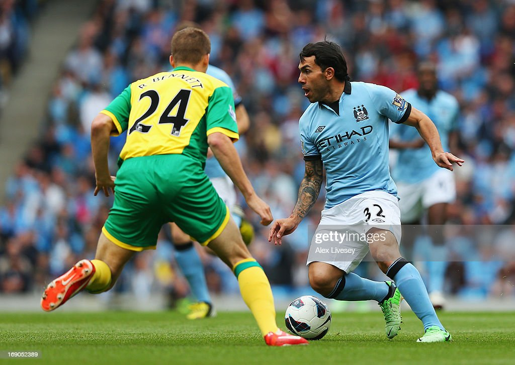 Carlos Tevez (R) of Manchester City holds off the challenge of Ryan Bennett (L) of Norwich City during the Barclays Premier League match between Manchester City and Norwich City at Etihad Stadium on May 19, 2013 in Manchester, England.