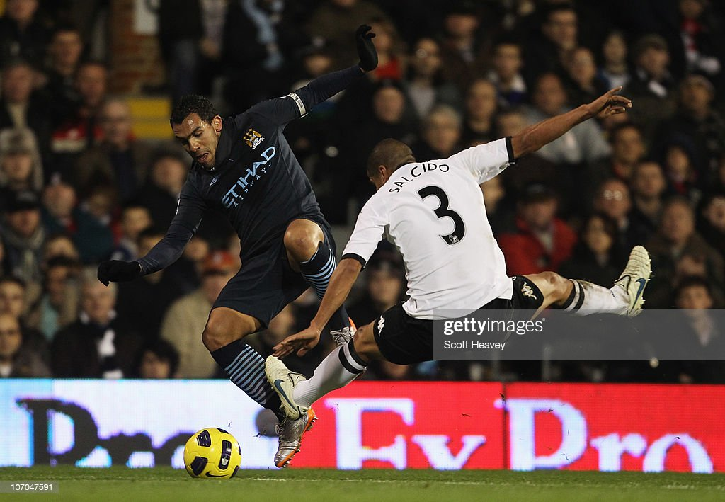 Carlos Tevez of Manchester City is challenged by Carlos Salcido of Fulham during the Barclays Premier League match between Fulham and Manchester City...