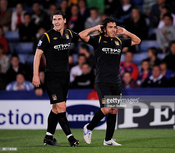 Carlos Tevez of Manchester City is congratulated by teammate Gareth Barry after scoring during the Carling Cup second round match between Crystal...
