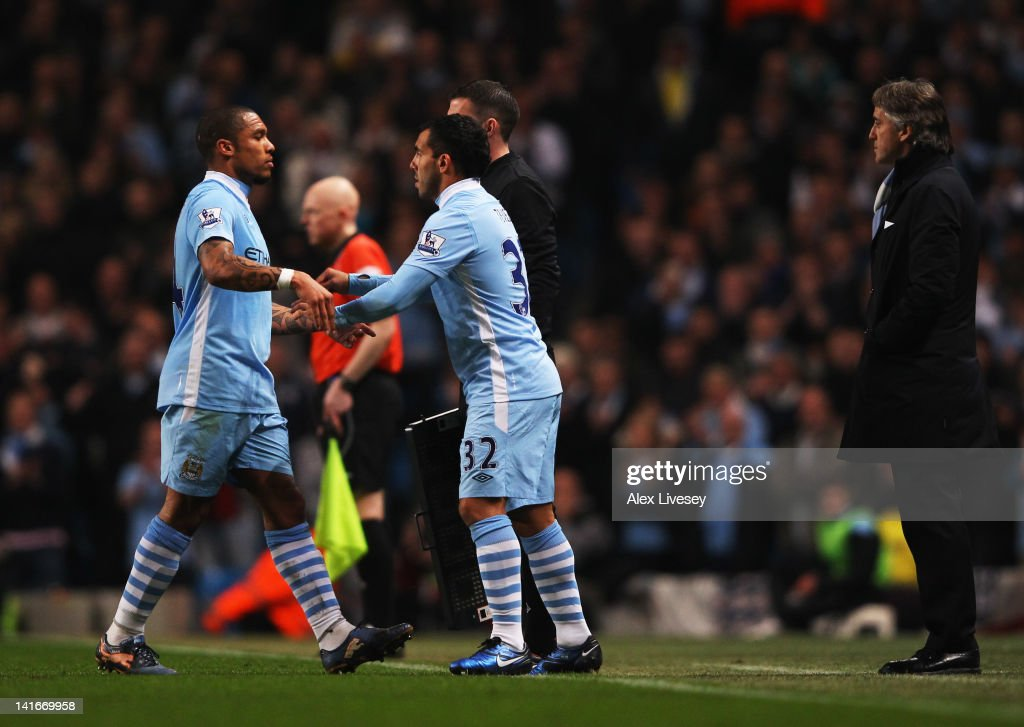 Carlos Tevez of Manchester City replaces Nigel de Jong as a substitute as Roberto Mancini manager of Manchester City looks onduring the Barclays...
