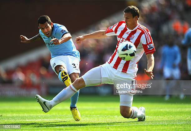 Carlos Tevez of Manchester City shoots at goal under pressure from Robert Huth of Stoke City during the Barclays Premier League match between Stoke...