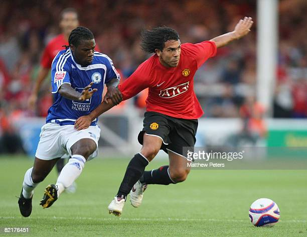 Carlos Tevez of Manchester United clashes with Aaron McLean of Peterborough United during the preseason friendly match between Peterborough United...