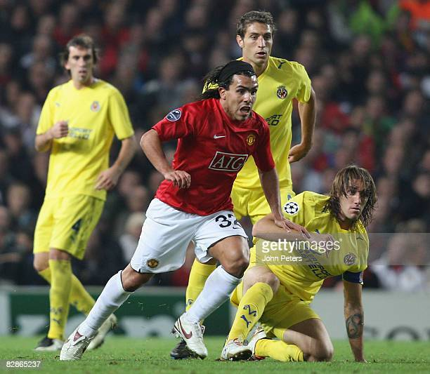 Carlos Tevez of Manchester United clashes with Gonzalo Rodriguez of Villarreal during the UEFA Champions League match between Manchester United and...