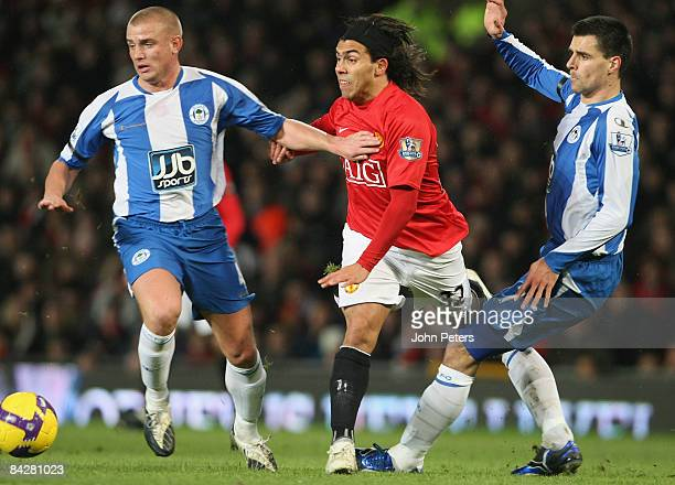 Carlos Tevez of Manchester United clashes with Lee Cattermole and Paul Scharner of Wigan Athletic during the Barclays Premier League match between...