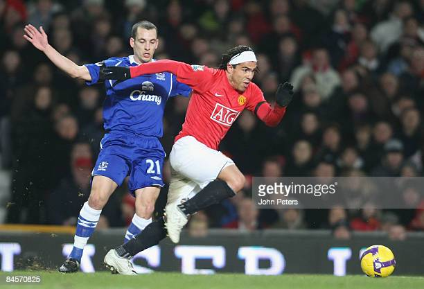 Carlos Tevez of Manchester United clashes with Leon Osman of Everton during the Barclays Premier League match between Manchester United and Everton...