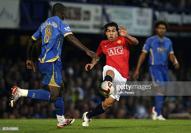 Carlos Tevez of Manchester United clashes with Pape Bouba Diop of Portsmouth during the FA Premier League match between Portsmouth and Manchester...