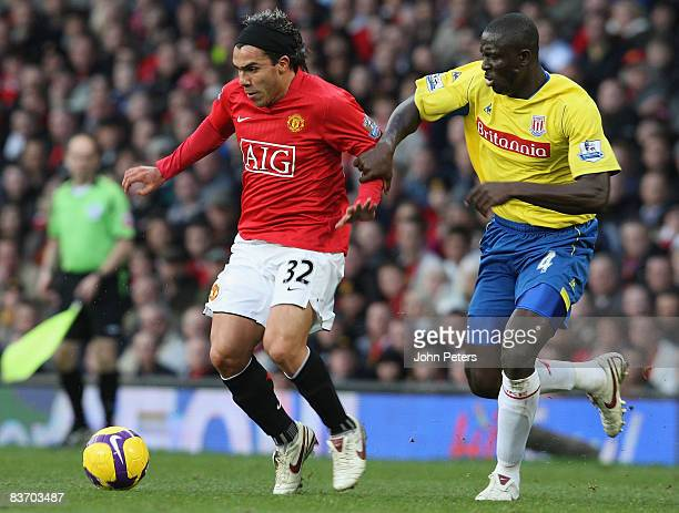 Carlos Tevez of Manchester United clashes with Seyi Olofinjana of Stoke City during the Barclays Premier League match between Manchester United and...