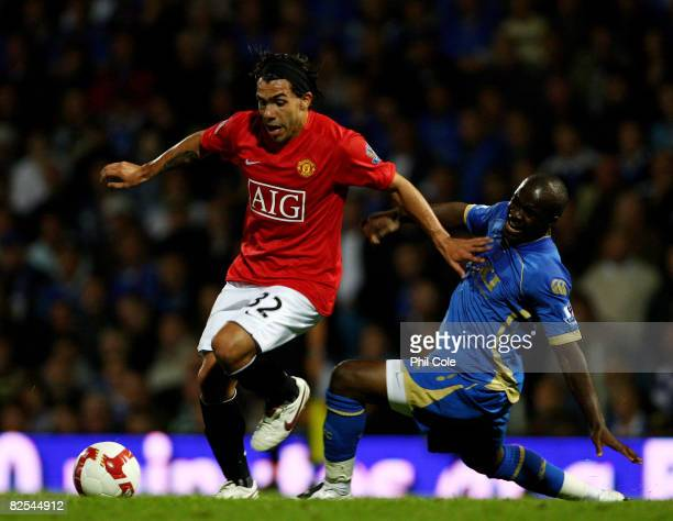 Carlos Tevez of Manchester United gets tackled by Lassana Diarra of Portsmouth during the Barclays Premier League match between Portsmouth and...