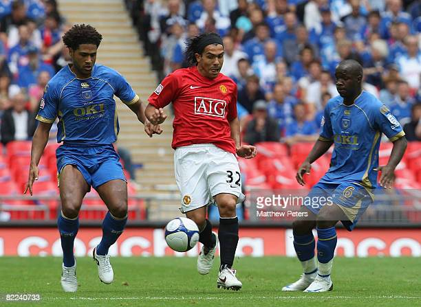 Carlos Tevez of Manchester United vies with Glen Johnson and Lassana Diarra of Portsmouth during the FA Community Shield match between Manchester...