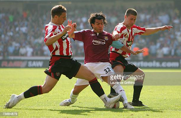 Carlos Tevez of West Ham United is challenged by Phil Jagielka and Nick Montgomery of Sheffield United during the Barclays Premiership match between...