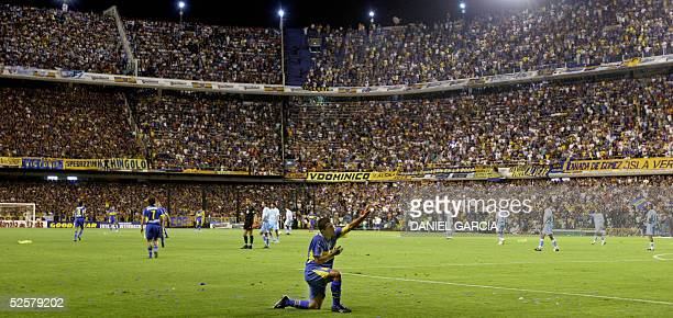 Carlos Tevez one of Boca Juniors' last idols offers his devotion to the team's fans after scoring the second goal against Bolivar de La Paz of...
