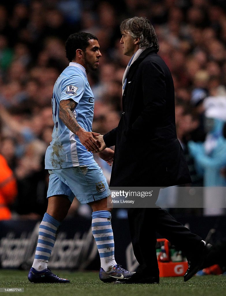 Carlos Tevez shakes hands with Manchester City Manager Roberto Mancini (R) as he is substituted during the Barclays Premier League match between Manchester City and Manchester United at the Etihad Stadium on April 30, 2012 in Manchester, England.