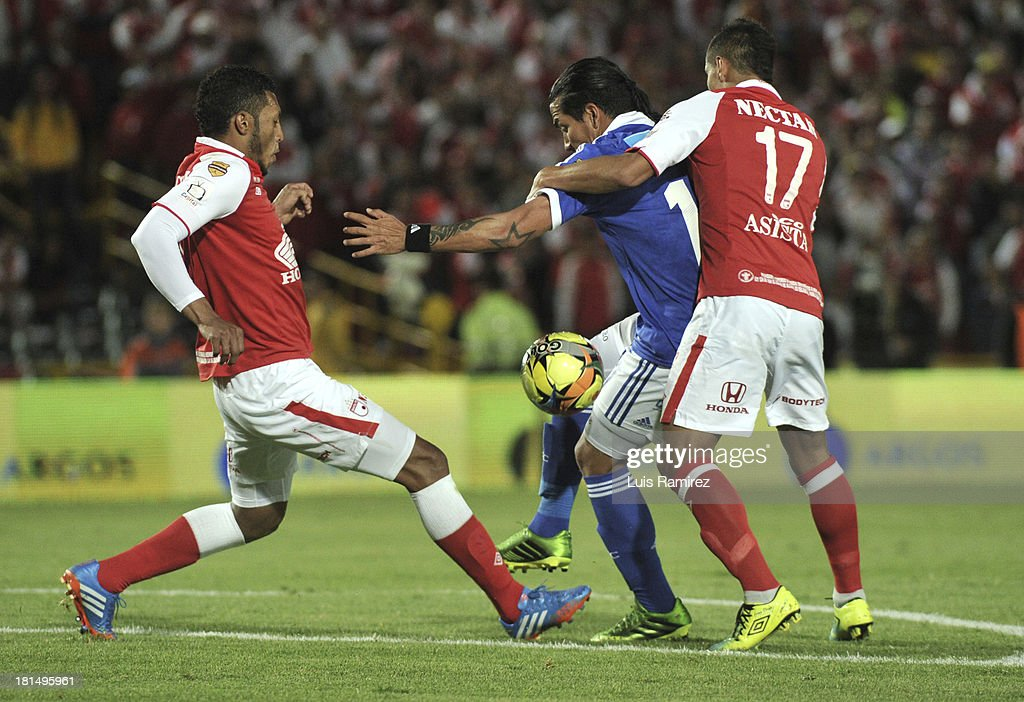 Carlos Valdes and Juan Roa of Independiente Santa Fe fight for the ball with Dayro Moreno of Millonarios during a match between Independiente Santa Fe and Millonarios as part of the Liga Postobon II at Nemesio Camacho Stadium on September 21, 2013 in Bogota, Colombia.