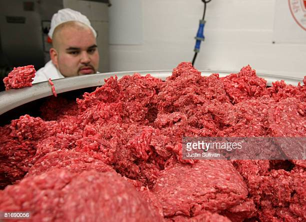 Carlos Vasquez monitors ground beef as it passes through a machine that makes hamburger patties at a meat packing and distribution facility June 24...