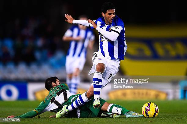 Carlos Vela Garrido of Real Sociedad competes for the ball with Victor Rodriguez of Elche FC during the La Liga match between Real Socided and Elche...