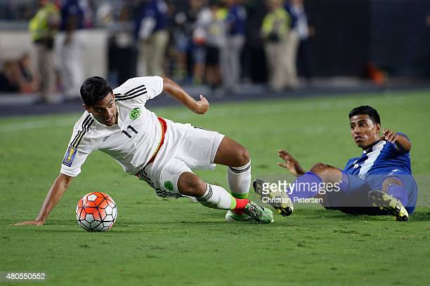 Carlos Vela of Mexico is tripped up by Moises Hernandez during the second half of the 2015 CONCACAF Gold Cup group C match at University of Phoenix...