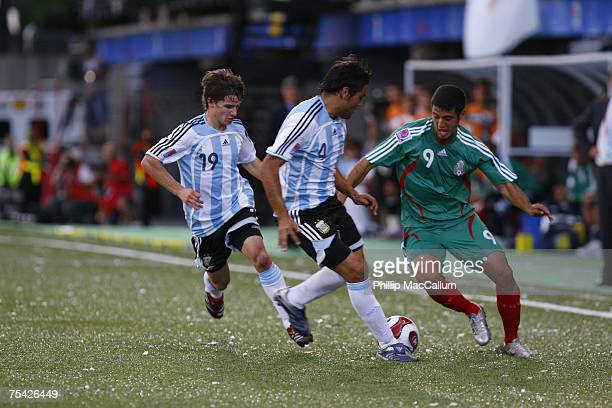 Carlos Vela of Mexico tries to carry the ball into the attacking zone around both Pablo Piatti and Gabriel Mercado of Argentina during the first half...