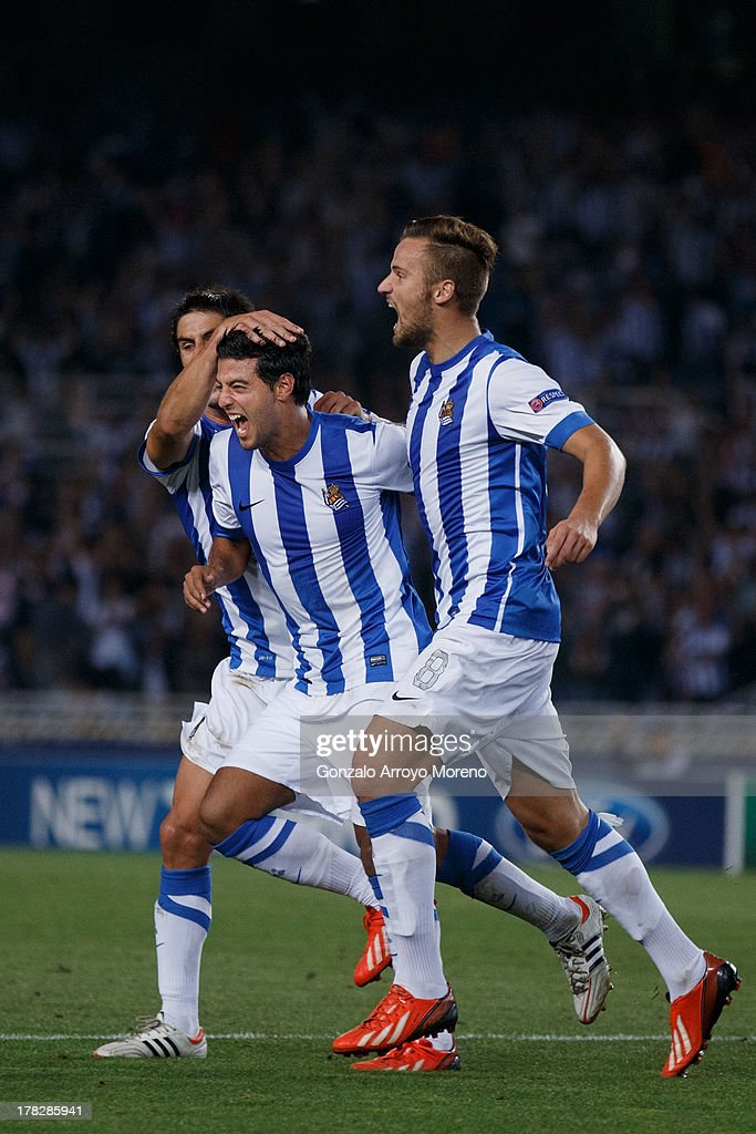 <a gi-track='captionPersonalityLinkClicked' href=/galleries/search?phrase=Carlos+Vela&family=editorial&specificpeople=2217707 ng-click='$event.stopPropagation()'>Carlos Vela</a> of Real Sociedad celebrates scoring their opening goal with teammates during the UEFA Champions League Play-offs second leg match between Real Sociedad and Olympique Lyonnais at Estadio Anoeta on August 28, 2013 in San Sebastian, Spain.