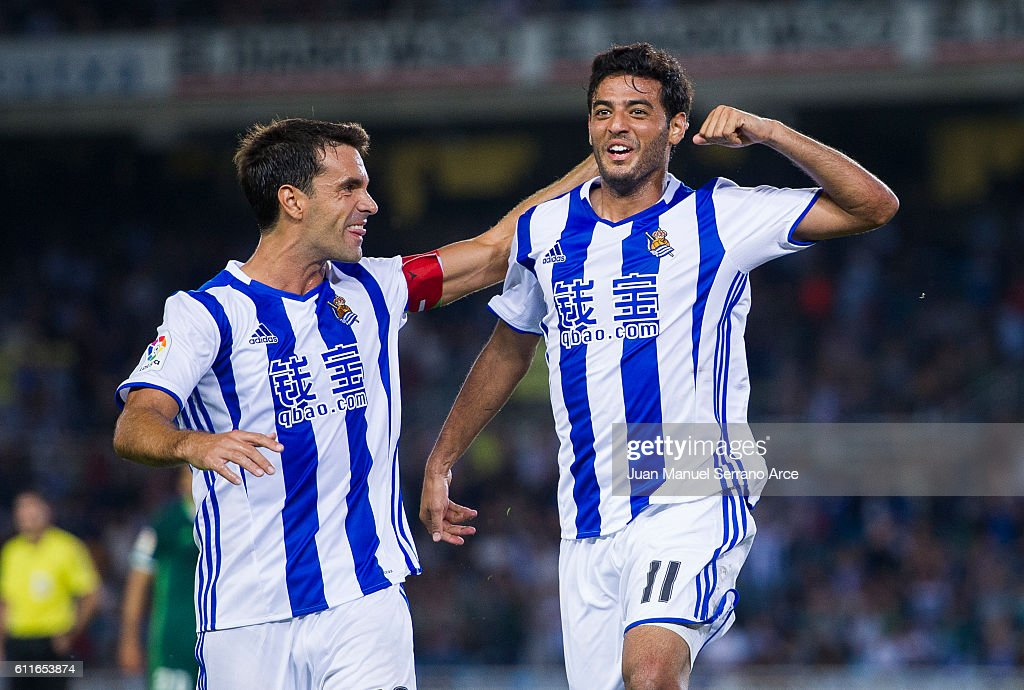 Carlos Vela of Real Sociedad celebrates with his teammate Xabier Prieto of Real Sociedad after scoring the opening goal during the La Liga match between Real Sociedad de Futbol and Real Betis Balompie at Estadio Anoeta on September 30, 2016 in San Sebastian, Spain.