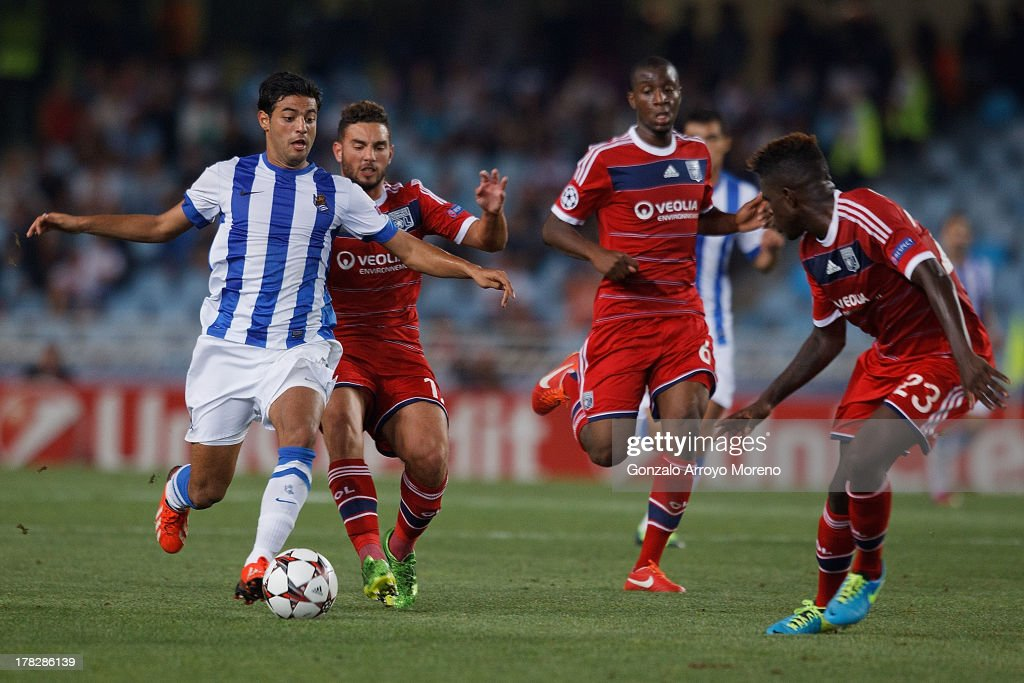 <a gi-track='captionPersonalityLinkClicked' href=/galleries/search?phrase=Carlos+Vela&family=editorial&specificpeople=2217707 ng-click='$event.stopPropagation()'>Carlos Vela</a> (L) of Real Sociedad competes for the ball with Jordan Ferri (2nd L) of Olympique Lyonnais during the UEFA Champions League Play-offs second leg match between Real Sociedad and Olympique Lyonnais at Estadio Anoeta on August 28, 2013 in San Sebastian, Spain.