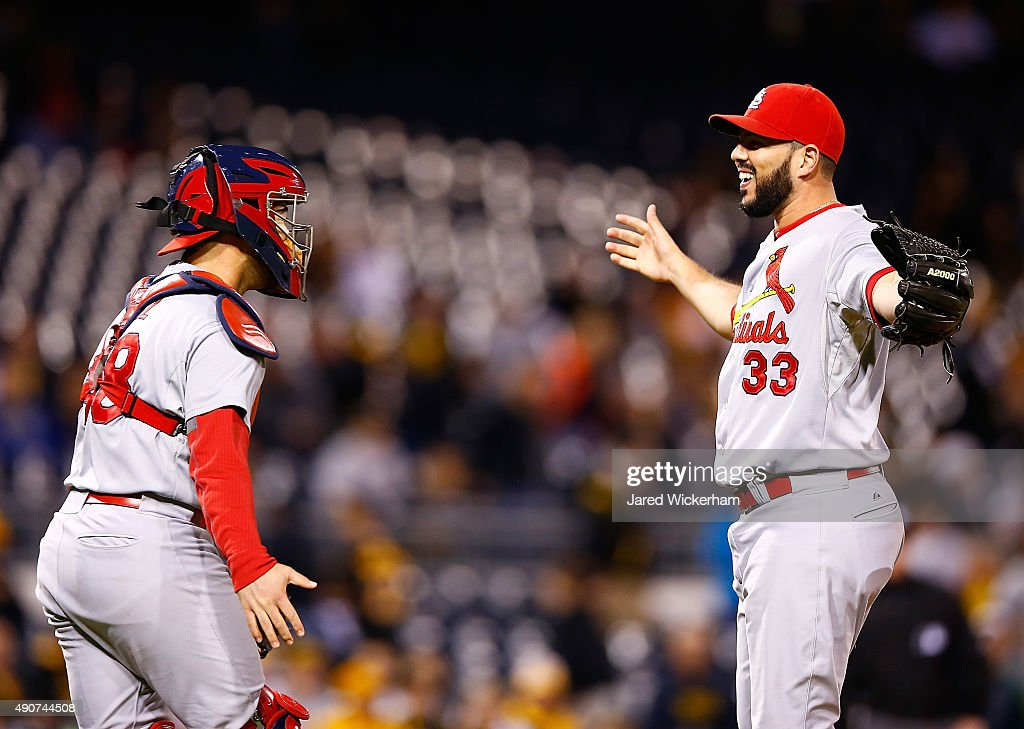 Carlos Villanueva #33 and Tony Cruz #48 of the St Louis Cardinals celebrate their division clinching 11-1 win against the Pittsburgh Pirates during the game at PNC Park on September 30, 2015 in Pittsburgh, Pennsylvania.