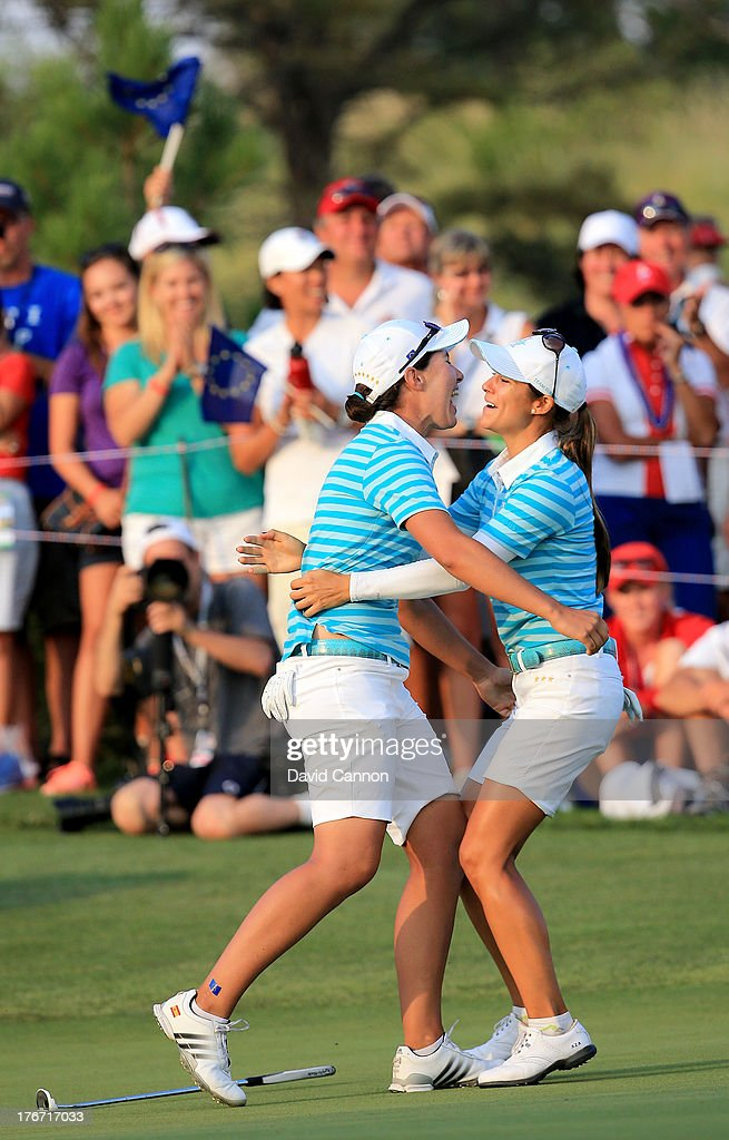 Carlota Ciganda of Spain (L) and the European Team elebrates with Azahara Munoz of Spain on the 18th green after Ciganda had holed a match winning birdie putt against Gerina Piller and Angela Stanford during the afternoon fourball matches for the 2013 Solheim Cup at The Colorado Golf Club on August 17, 2013 in Parker, Colorado.