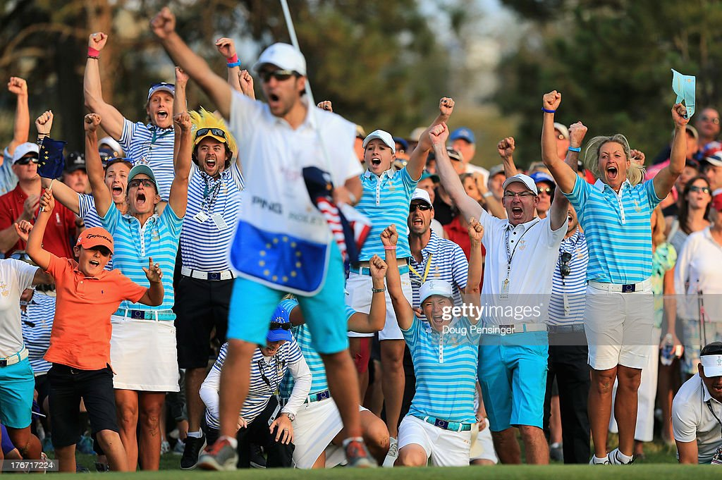 Carlota Ciganda's caddie Javier Urquizu begins to celebrate as the European Team members and caddies erupt behind him as Carlota Ciganda of Spain and the European Team makes a birdie putt on the 18th hole to win the match with her teammate Azahara Munoz of Spain over Gerina Piller and Angela Stanford of the United States Team during the afternoon four-ball matches at the 2013 Solheim Cup on August 17, 2013 at the Colorado Golf Club in Parker, Colorado.