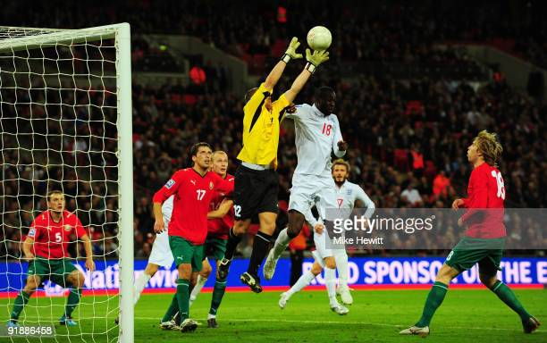 Carlton Cole of England challenges goalkeeper Yuri Zhevnov of Belarus during the FIFA 2010 World Cup Qualifying Group 6 match between England and...