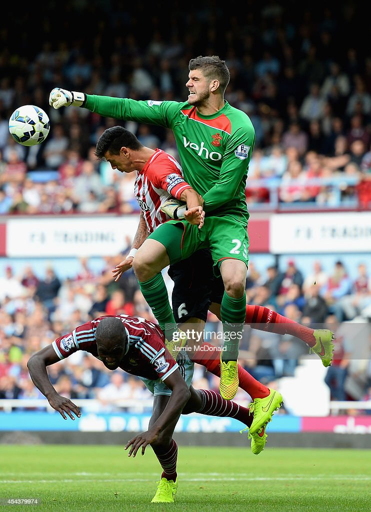 Carlton Cole of West Ham battles with Fraser Forster and Jose Fonte of Southampton during the Barclays Premier League match between West Ham United and Southampton at Boleyn Ground on August 30, 2014 in London, England.