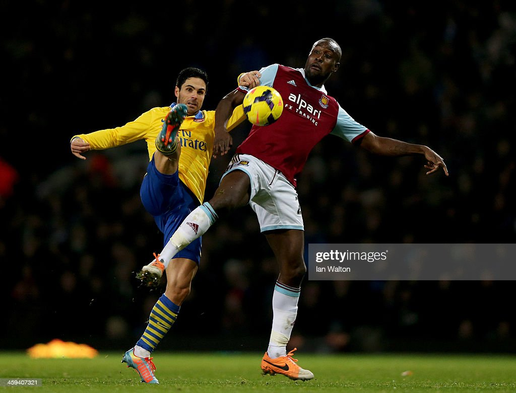 Carlton Cole of West Ham United battles with Mikel Arteta of Arsenal during the Barclays Premier League match between West Ham United and Arsenal at Boleyn Ground on December 26, 2013 in London, England.