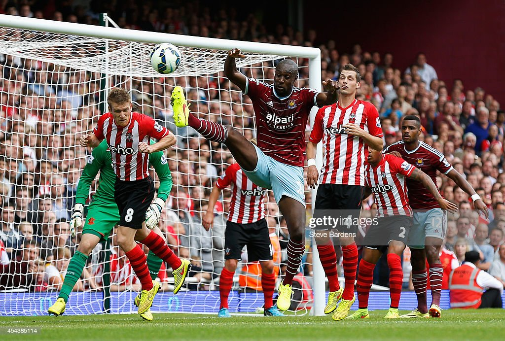 Carlton Cole of West Ham United challenges Steven Davis of Southampton during the Barclays Premier League match between West Ham United and Southampton at Boleyn Ground on August 30, 2014 in London, England.
