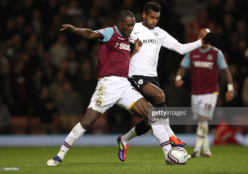 Carlton Cole of West Ham United is challenged by Ricardo Vaz Te of Barnsley during the npower Championship match between West Ham United and Barnsley at the Boleyn Ground on December 17, 2011 in London, England.