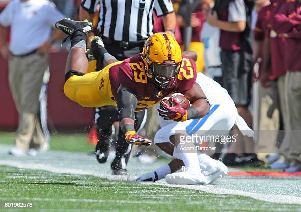 Carlton Djam of the Minnesota Golden Gophers flies after being tripped by Devin Brockington of the Indiana State Sycamores in the fourth quarter at...