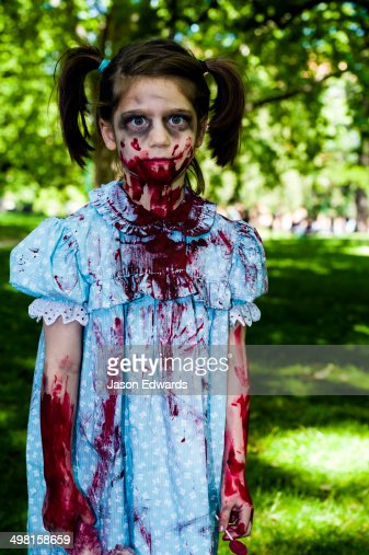 A blood-soaked zombie girl with pigtails in a pretty blue dress at a festival.