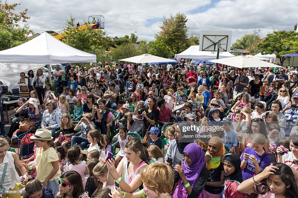 A crowd gathers to watch children perform theatre at a school fete.
