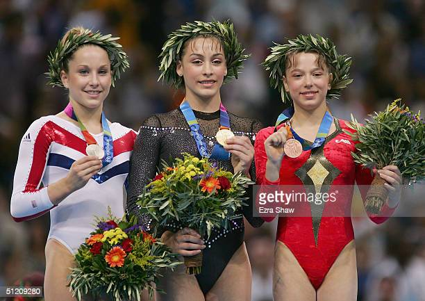 Carly Patterson of United States Catalina Ponor of Romania and Alexandra Georgiana Eremia of Romania receive their medals for the women's artistic...