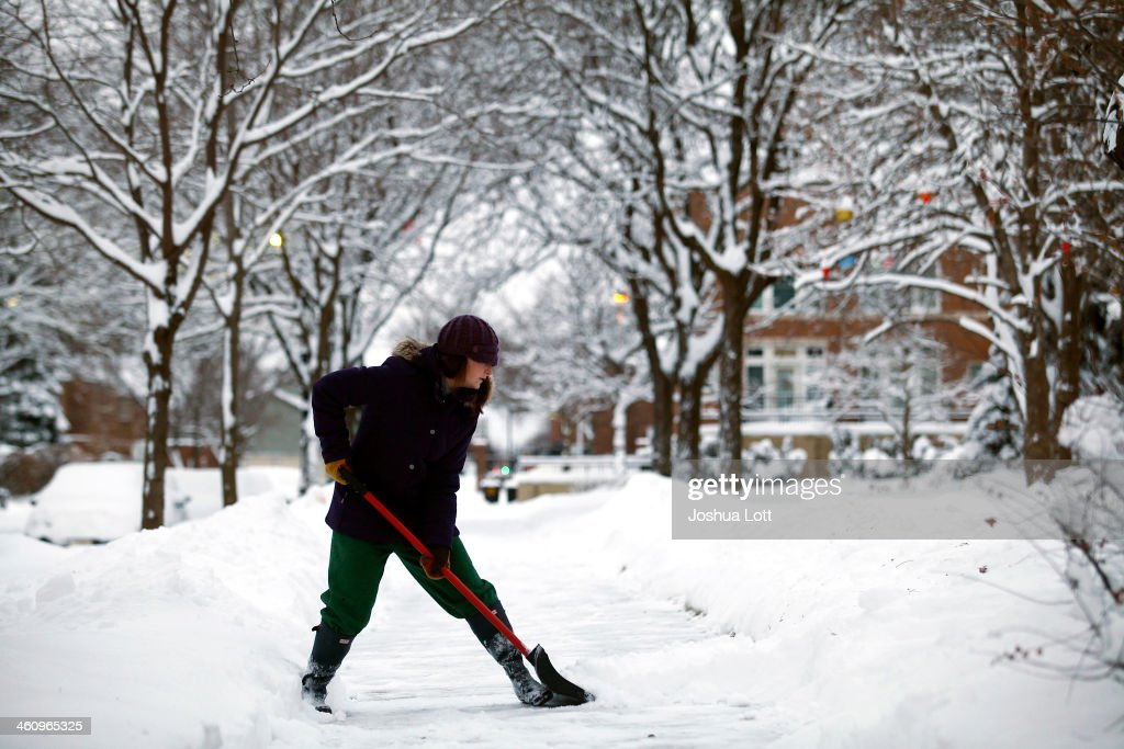 Carly Strachan shovels several inches of snow from her sidewalk as the area deals with record breaking freezing weather January 6, 2014 in Detroit, Michigan. Michigan and most of the Midwest received their first major snow storm of 2014 last week and subzero temperatures are expected most of this week with wind-chill driving temperatures down to 50-70 degrees below zero. A 'polar vortex' weather pattern is bringing some of the coldest weather the U.S. has had in almost 20 years.