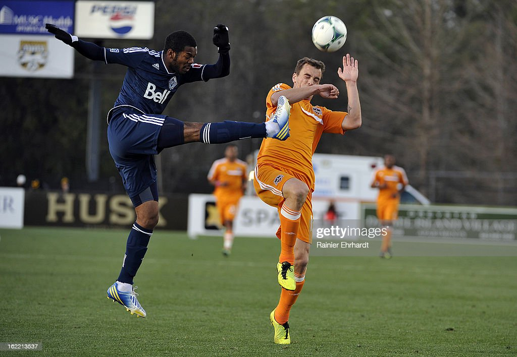 Carlyle Mitchell #19 of the Vancouver Whitecaps FC and Cam Weaver #15 of the Houston Dynamo battle for the ball during the first half of a game on February 20, 2013 in Charleston, North Carolina.