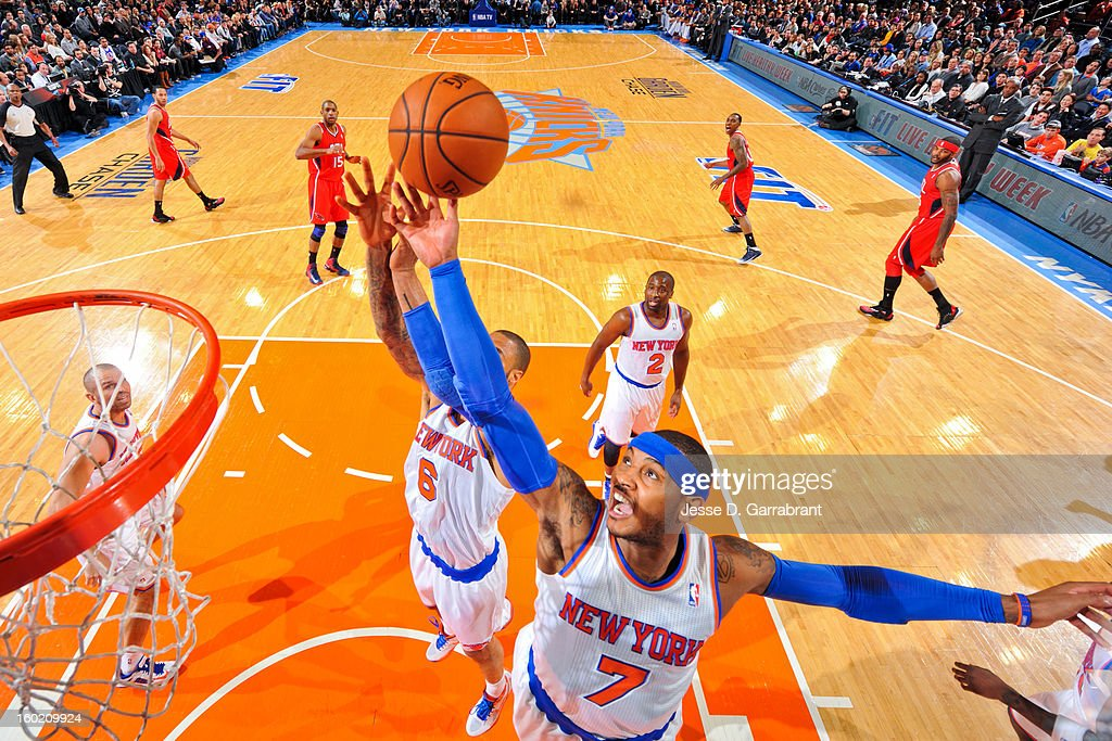 Carmelo Anthony #7 and Tyson Chandler #6 of the New York Knicks reach for a rebound against the Atlanta Hawks at Madison Square Garden on January 27, 2013 in New York, New York.