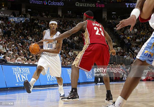 Carmelo Anthony of the Denver Nuggets drives against LeBron James of the Cleveland Cavaliers in the first quarter December 2 2003 at the Pepsi Center...