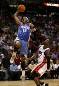 Carmelo Anthony of the Denver Nuggets dunks over Dwyane Wade of the Miami Heat at American Airlines Arena on November 14 2006 in Miami Florida NOTE...