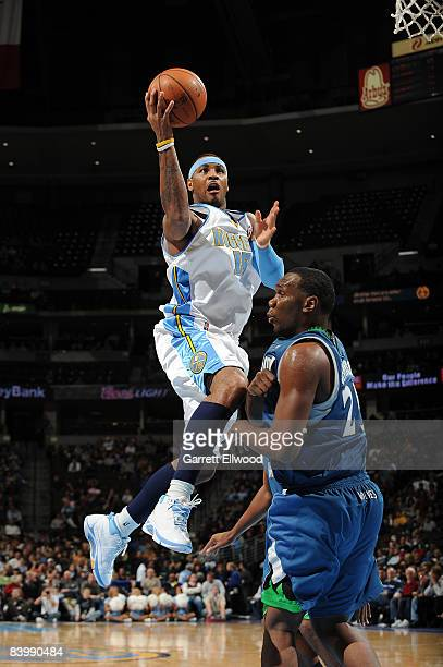 Carmelo Anthony of the Denver Nuggets goes to the basket against Al Jefferson of the Minnesota Timberwolves at the Pepsi Center December 10 2008 in...