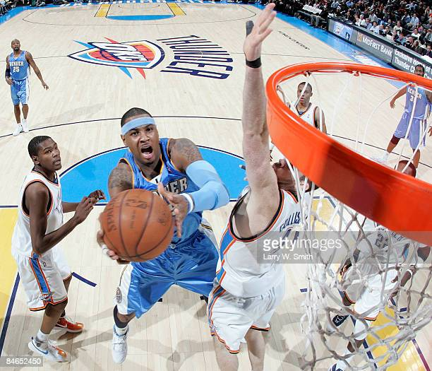 Carmelo Anthony of the Denver Nuggets goes to the basket against Nick Collison of the Oklahoma City Thunder at the Ford Center on February 4 2009 in...