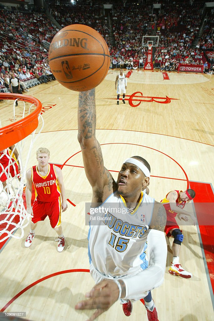 Carmelo Anthony #15 of the Denver Nuggets shoots the ball over Brad Miller #52 and Chase Budinger #10 of the Houston Rockets on February 14, 2011 at the Toyota Center in Houston, Texas.