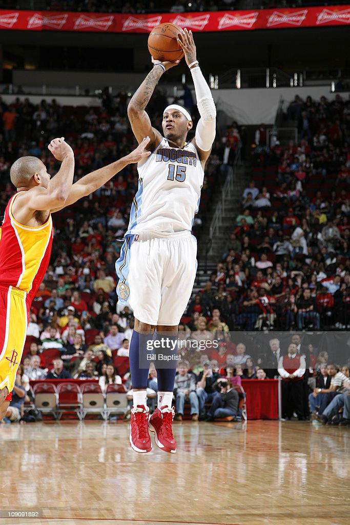 Carmelo Anthony #15 of the Denver Nuggets shoots the ball over Shane Battier #31 of the Houston Rockets on February 14, 2011 at the Toyota Center in Houston, Texas.