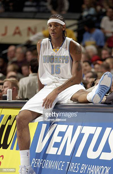 Carmelo Anthony of the Denver Nuggets waits to get into the game against the Boston Celtics at the Pepsi Center on December 7 2003 in Denver Colorado...