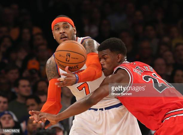 Carmelo Anthony of the New York Knicks and Jimmy Butler of the Chicago Bulls battle for the ball at Madison Square Garden on December 21 2012 in New...