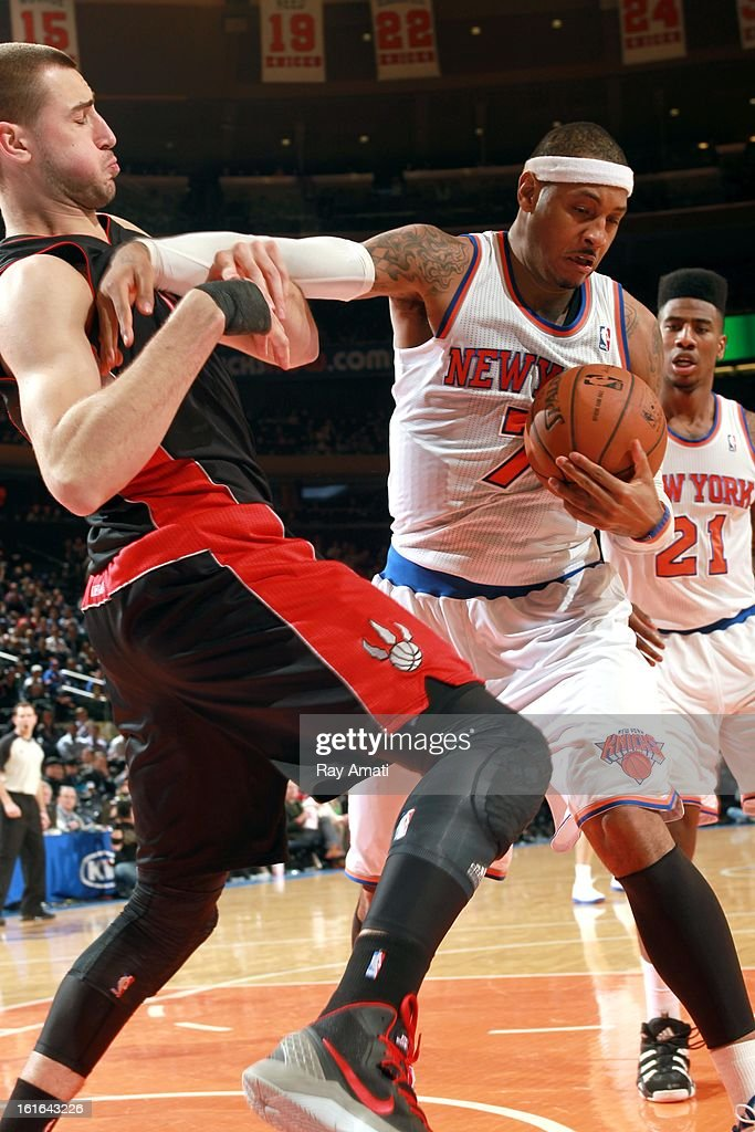 Carmelo Anthony #7 of the New York Knicks battles for the ball control against Jonas Valanciunas #17 of the Toronto Raptors on February 13, 2013 at Madison Square Garden in New York City.